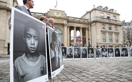 Members of France's parliament hold photographs portraying civil victims of air raid bombings around the world as they take part in a gathering for the civil victims of explosive devices, called by the French Non-governmental organisation (NGO) Handicap International, outside the French National Assembly, in Paris, on November 7, 2018. Paris will host world leaders and NGOs for the first Peace Forum on November 11 - 13. Photo: Jacques Demarthon/AFP
