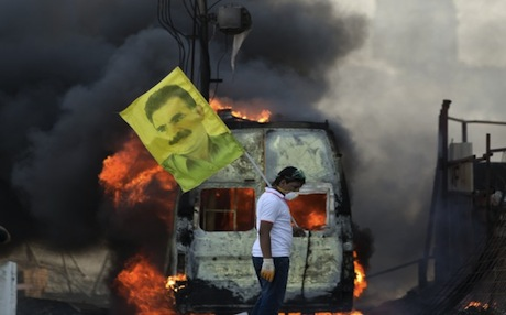A Kurdish protester holds a picture of jailed PKK leader Abdullah Ocalan near a burning vehicle at Istanbul's Taksim Square. Photo: AP