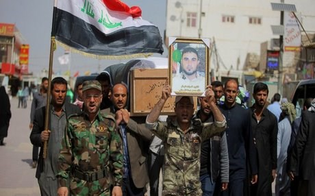 The Shiite Badr Brigade, backed by Iran, at a funeral for a dead fighter. AP photo.