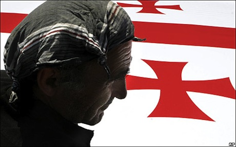 In Tbilisi, Georgia, a worker installs a flag in preparation for independence day celebrations, 2008. Photo: AP