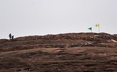 Kurdish YPG forces plant their flag on a hill outside Kobani after expelling ISIS militants from the city. Photo: AFP