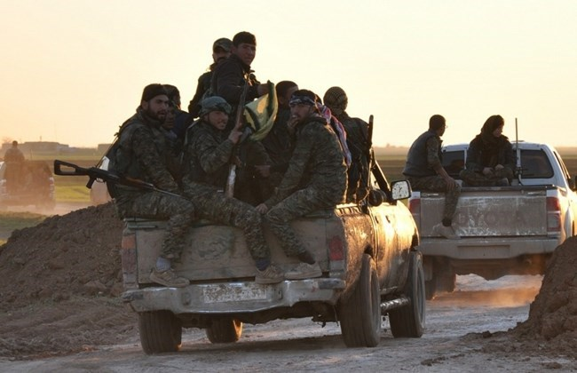 People's Protection Units (YPG) fighters drive at sunset on the outskirts of Tal Hamis, southeast of the city of Qameshli, on February 26, 2015, after they retook parts of the town following six days of clashes with ISIS jihadis in Syria's Hassakeh province.Photo: AFP.