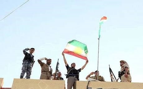 Peshmerga soldiers hoist the Kurdistan flag over the mayor's office in the town of Makhmour after its liberation from ISIS militants, August 2014. Rudaw photo