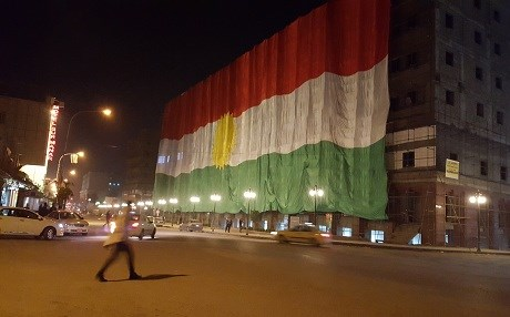 A large Kurdish flag hanging on the side of an unfinished market building in downtown Erbil on the Kurdish national flag day, December 17, 2015. Photo by Ayub Nuri