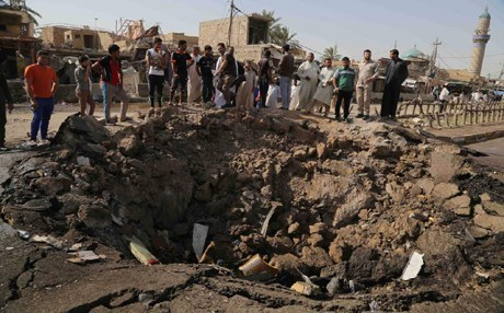 Civilians inspect a crater caused by a suicide car bombing at a busy market in the Diyala province. Photo: AP