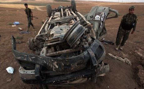Peshmerga forces inspect an ISIS vehicle destroyed in an airstrike. Photo: AFP