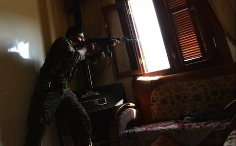 A Kurdish fighter from the People's Protection Units (YPG) fires towards Syrian government forces inside a building in the majority-Kurdish Sheikh Maqsud district of Aleppo, on April 21, 2013. Photo: AFP