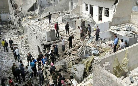 People gathered in the ruins of an attack on a civilian neighborhood in Aleppo. Photo: AP