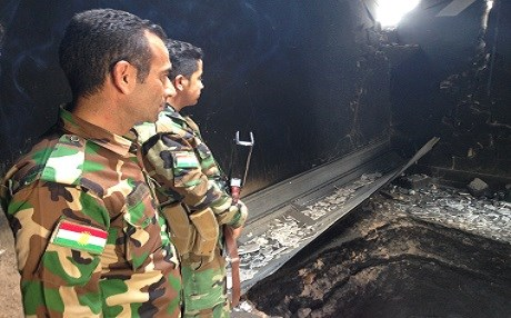 Two Kurdish Peshmerga soldiers inspect an underground ISIS tunnel in a village east of Mosul. Photo by Ayub Nuri