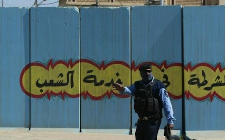 An Iraqi policeman man's a checkpoint in the multiethnic city of Kirkuk. On the blast wall behind him it reads in Arabic, 'The police are at the service of people'. Photo: Rudaw