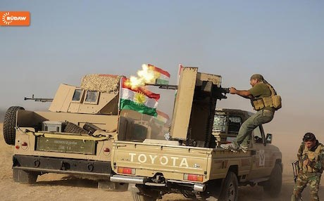 A Kurdish Peshmerga firing doshka machine-gun into an ISIS-controlled village on the Khazir front east of Mosul. Photo by Farzin Hassan