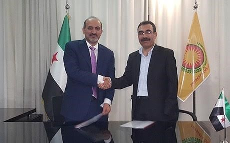 Rojava envoy Aldar Khalil shaking hands with Ahmed Jarba, head of the Al-Ghad Front, in Cairo.
