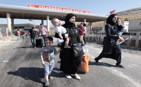 Syrian refugees pass through the Turkish Cilvegozu gate border . AP photo