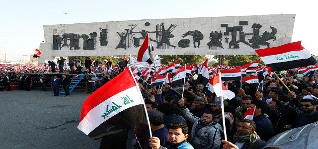 Iraqi supporters of the Sadrist movement hold national flags during a demonstration in Baghdad's Tahrir Square. Photo:AFP / Sabah Arar