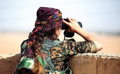 A member of the YPJ, the women's arm of the Kurdish YPG, survey's a battlefield 40km from Raqqa last November. Photo: Delil Souleiman/AFP