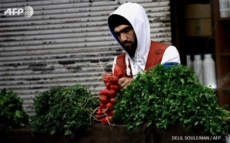 A vegetable-seller in Qamishli, Rojava, northern Syria. Photo: Delil Souleiman/AFP