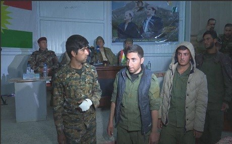 Four of the five fighters of the Shingal Protections Units (YBS) walk out of a hall where Peshmerga commanders hold a press conference on Saturday in Shingal.  They were released based on an order from President Masoud Barzani, a Peshmerga commander said. Photo:Rudaw video.