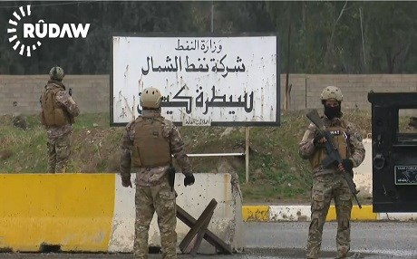 Members of the security forces of the Kurdish Patriotic Union of Kurdistan  guard the main gate of the Iraqi North Oil Company on Thursday.  Photo: Rudaw video