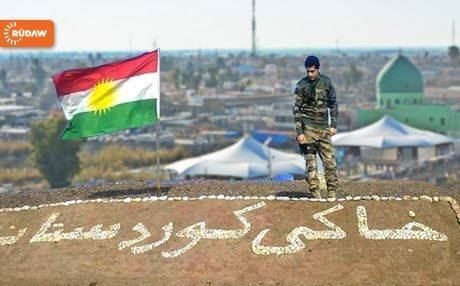 A Kurdish Peshmerga planting the flag of Kurdistan in Kirkuk, June 2014. Photo: Rudaw