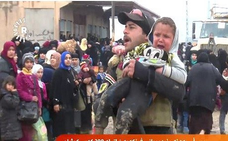 An Iraqi soldier carries a child separated from his family following Thursday's deadly air strikes in Mosul.