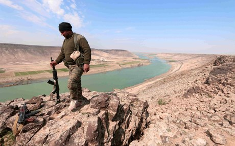 A fighter stands atop the Tabqa Dam in Syria. Photo: AFP