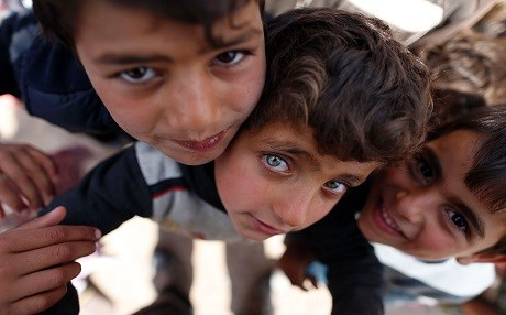 Displaced Iraqi children, who fled the ongoing Mosul offesnive, pose for the camera at the Hasan Sham camp , 30 kilometres east of the city. Photo: AFP/Ahmad Gharabli