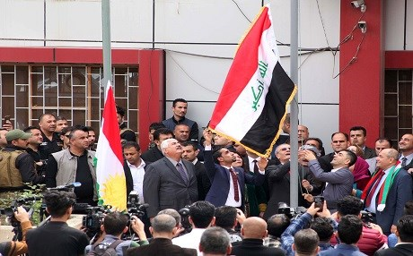 Kirkuk Governor Najmadin Karim raises the Iraqi flag to fly next to the Kurdish flag over a government building in the northern Iraqi city of Kirkuk. Photo: AFP/Mariwan Ibrahim