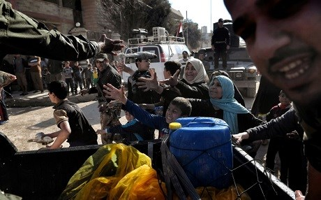 Iraqi forces distribute food aid to west Mosul resident. Photo: Aris Messinis/AFP