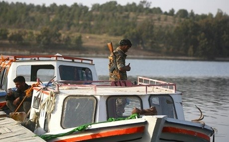 Members of Syrian Democratic Forces stand on a boat at the Lake Assad. Photo: AFP