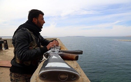 A Coalition-partnered anti-ISIS ground fighter looks over Tabqa Dam in northern Syria. Photo: Delil Souleiman | AFP