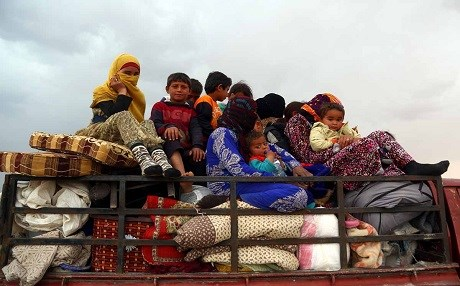 Children from near Tabqa in Syria ride in a truck. Photo: Delil Souleiman | AFP