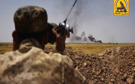 A Hashd al-Shaabi fighter peers at a distant strike in northern Iraq. Photo: Iraqi PMU