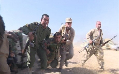 Kurdish Peshmerga carrying away a wounded fellow soldier during battle with ISIS militants. Photo: Rudaw