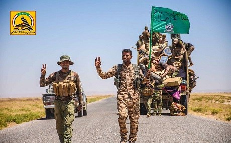 Members of the mainly Shiite Hashd al-Shaabi forces gesture as they drive against the ISIS positions near the Iraqi-Syrian border. Photo: Hashd media office.