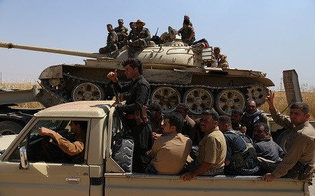 Regular Peshmerga forces and Kurdish volunteers heading to a frontline south of Kirkuk to defend the area against ISIS takeover, 2014. Photo by Farzin Hassan/Rudaw