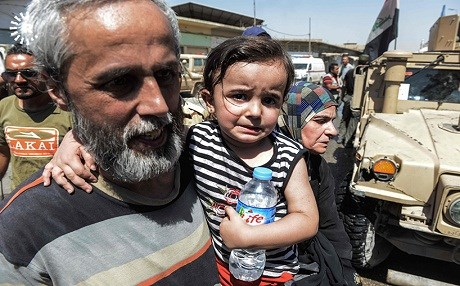 A man carries a child after fleeing from western Mosul in late June. Photo: Mohamed El-Shahed | AFP
