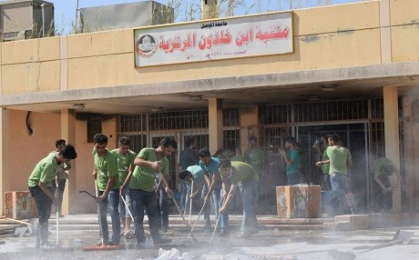 Volunteers clean debris from the library at Mosul's university. Photos: Mustafa Khaled