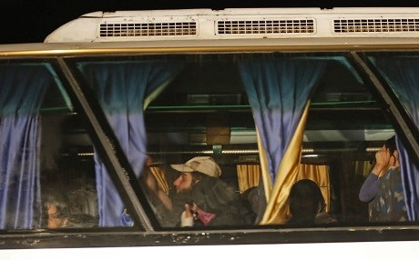 Members of theISIS group and their families are seen in a bus in Qara area in Syria's Qalamoun region on August 28, 2017 as they are transported to Deir Ez-Zor following a deal between ISIS militants and the Lebanese Hezbollah group, and the Syrian regime. Photo: AFP/ Louai Beshara