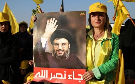 A supporter of the Lebanese Shiite movement Hezbollah holds a poster bearing a portrait of Hassan Nasrallah as she attends on August 31, 2017 a rally in Baalbek to celebrate the return of its fighters after fighting a week-long offensive against the ISIS group on Syria's side of the Lebanese border. Photo: AFP