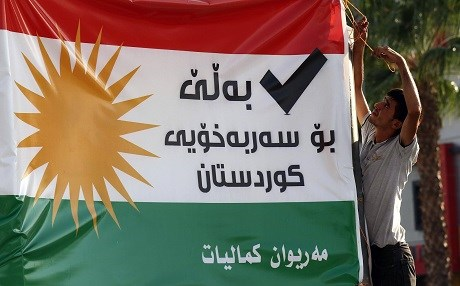 A man in Erbil hangs a banner that advocates for a 'Yes' vote in the Kurdistan Region's upcoming independence referendum. Photo: Safin Hamed | AFP