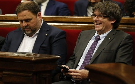 President of the Catalan Government Carles Puigdemont (right) laughs beside Catalan regional vice-president Oriol Junqueras during a session at the Catalan parliament to debate and vote a secession law, in Barcelona, on September 7. Photo: Pau Barrena | AFP