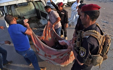 Iraqi security forces and civilians carry the body of a victim from the Nasiriyah attack in southern Iraq on September 14. Phto: Haidar Hamdani | AFP
