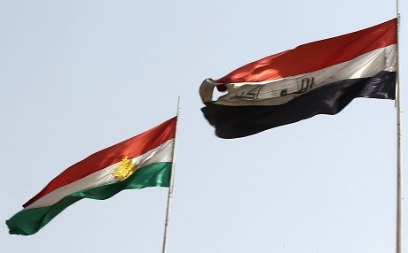 The flags of Kurdistan and Iraq fly next to eachother in oil-rich Kirkuk on September 26. Photo: Ahmad al-Rubaye | AFP