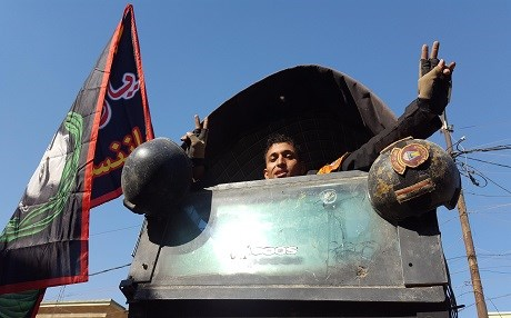 A member of the Iraqi Golden Brigade shows the victory sign on top of an American armored Humvee adorned with a Shiite religious flag of Imam Hussein. Mosul/Nov. 2016. Photo: Rudaw
