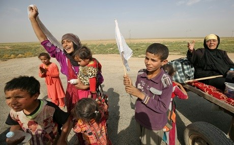 Members of an Iraqi family, displaced from the outskirts of Islamic State group stronghold Hawija, raise white flags while travelling on the road outside the town on October 3, 2017. AFP / AHMAD AL-RUBAYE