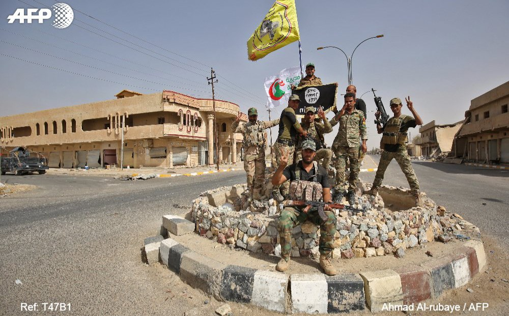 Iraqi forces pose in Hawija town, retaken from ISIS on October 5. Photo: Ahmad al-Rubaye/AFP