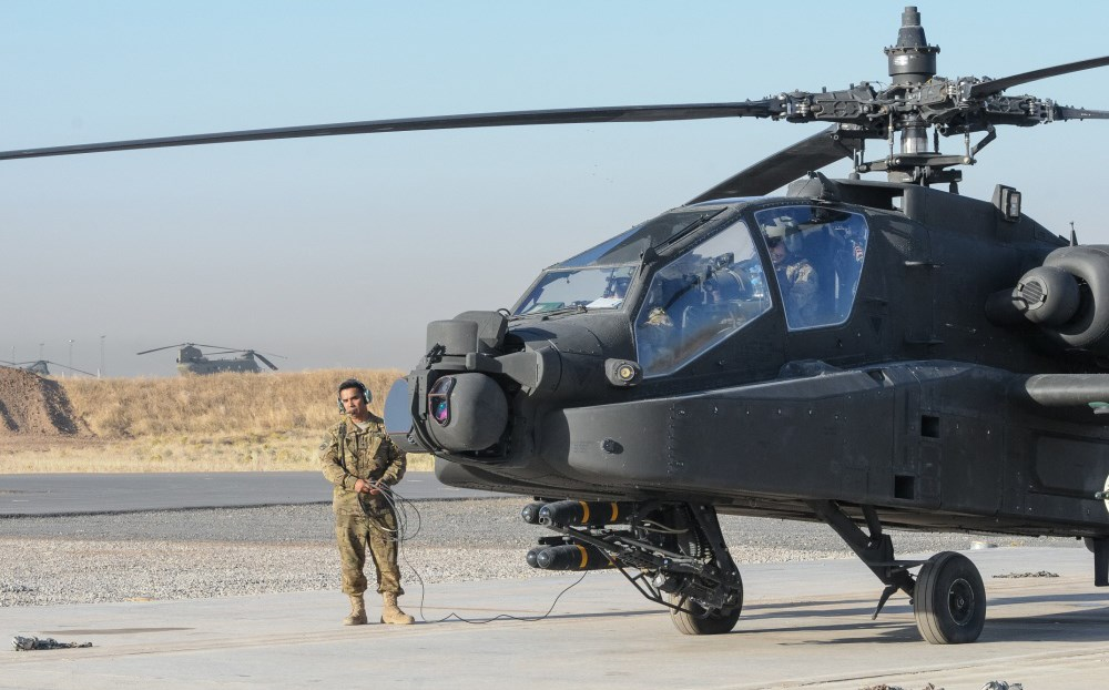 Coalition soldiers conduct pre-flight inspections of an Apache helicopter in Erbil in July. Photo: Capt. Stephen James/US Army
