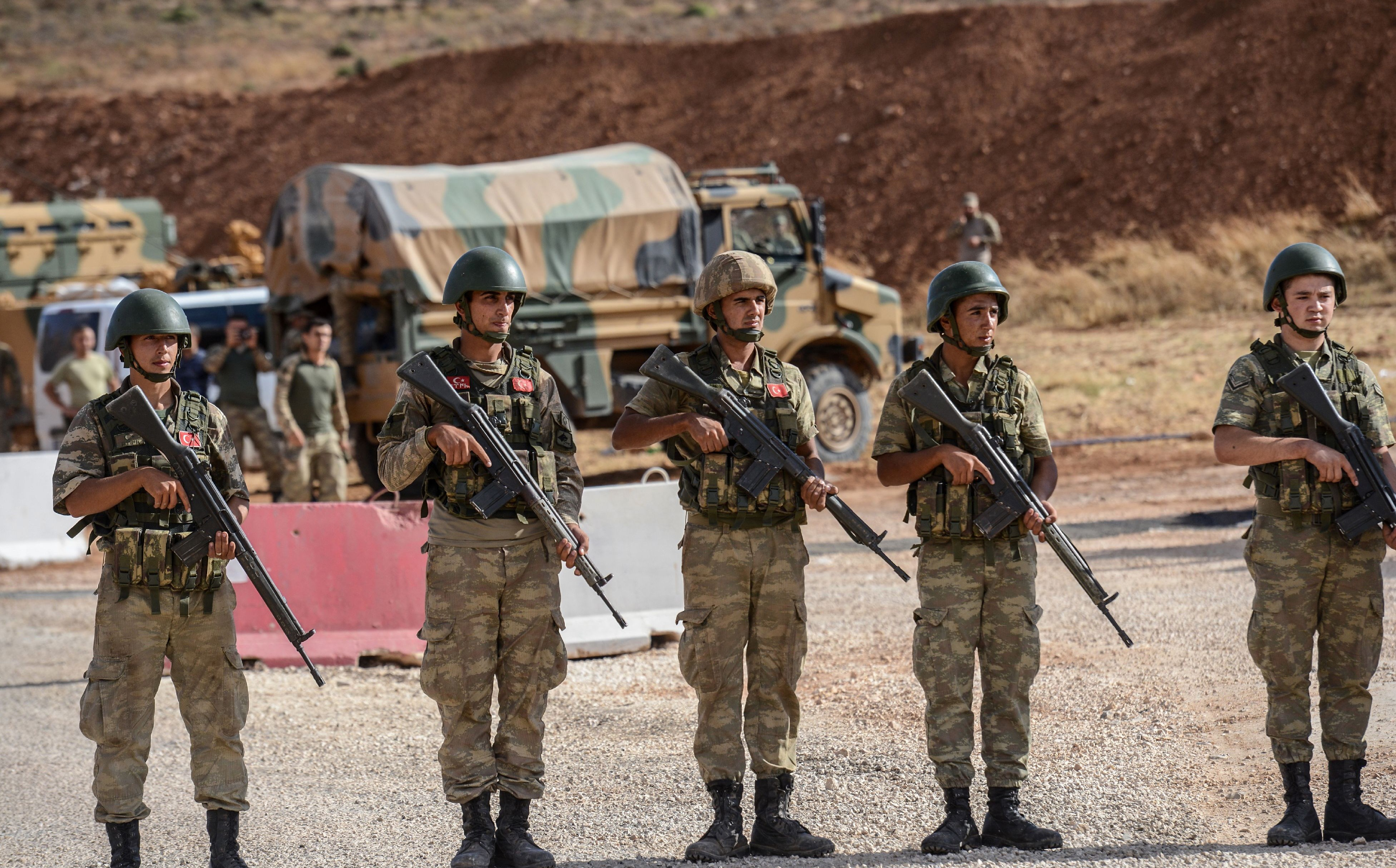 Turkish soldiers stand near armoured vehicles near the Turkey-Syria border on Tuesday. Photo: Ilyas Akengin/AFP