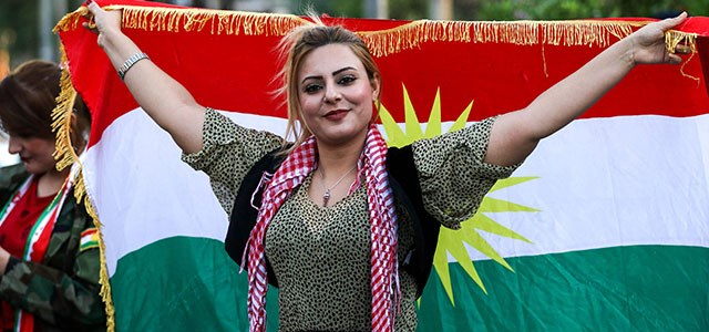 An Iraqi Kurdish woman poses with the flag of of the Kurdistan region during a demonstration outside the UN Office in Erbil on October 21, 2017, protesting against the escalating crisis with Baghdad. Photo: AFP / Safin Hamed