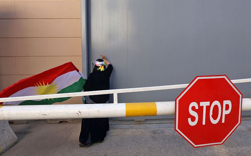 A protester beats on a gate at the US Consulate in Erbil as Kurds felt let down by the United States. Photo: Safin Hamed/AFP